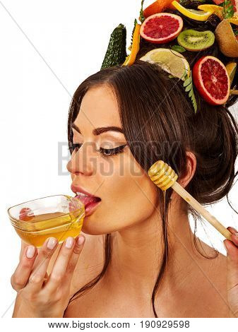 Honey facial mask with fresh fruits for hair and skin on woman head. Face of girl with beautiful face hold honeycombs for homemade organic skin and hair therapy. Medical properties of honey concept.