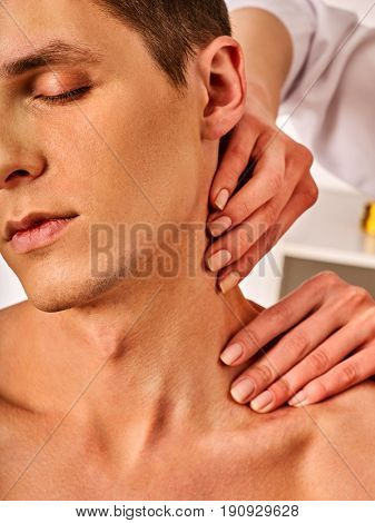 Shoulder and neck massage for man in spa salon. Doctor making therapy in rehabilitation center . Folded towels in the background. Correction of dislocation of neck by experienced specialist.
