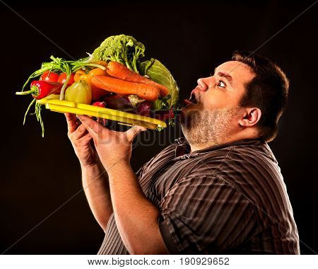 Diet fat man eating healthy food with vegetables for overweight male. Male trying to lose weight first time .Hungry person ready to eat everything. Vegetables for diet in unlimited quantities.