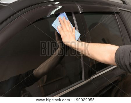 Worker polishing tinted car window