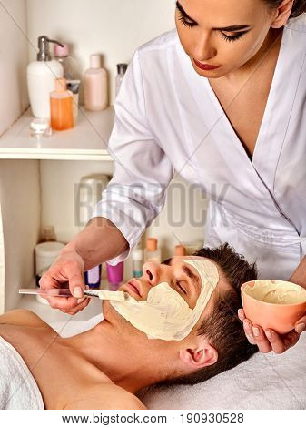 Mud facial mask of man in spa salon. Massage with clay full face. Girl on with therapy room. Man lying on spa bed. Beautician with bowl therapeutic procedure . Ointment against acne.