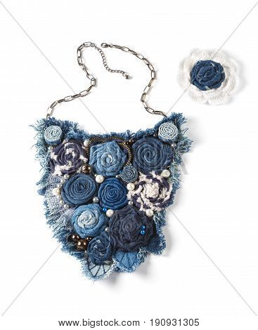 Large pendant consisting of jean flowers and brooch on white background