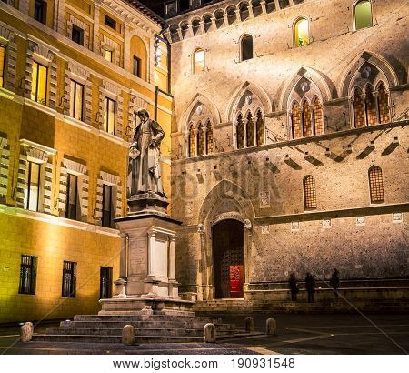 Male statue at night in Siena Italy