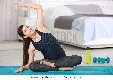 Young beautiful pregnant woman doing yoga exercise in the room