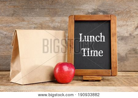 Small blackboard with text LUNCH TIME and paper bag on wooden background
