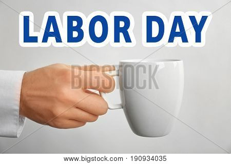 Concept of LABOUR DAY. Man holding cup on light background, closeup