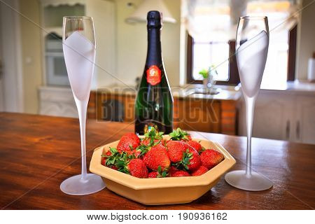 Two flutes of champagne with strawberries on the table