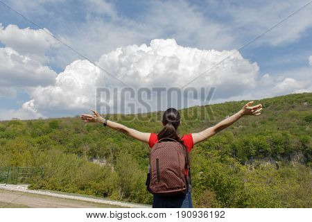 Young hiker girl with backpack enjoying and looking to the sky with clouds. Active hikers