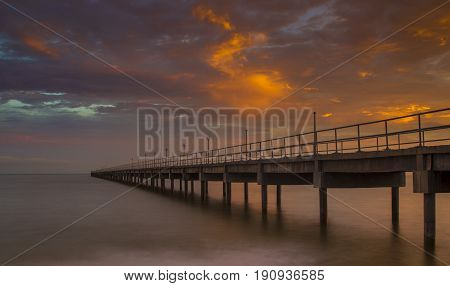 Long exposure bridge against sun setting clouds