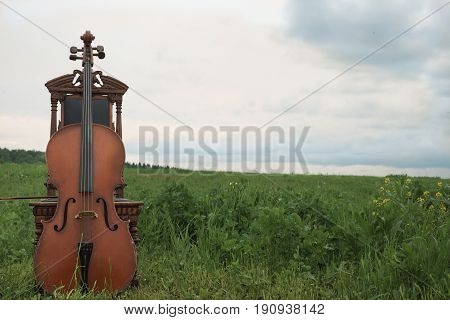 Abandoned vintage cello and wooden carved chair. A filed landscape with overcast sky in the background