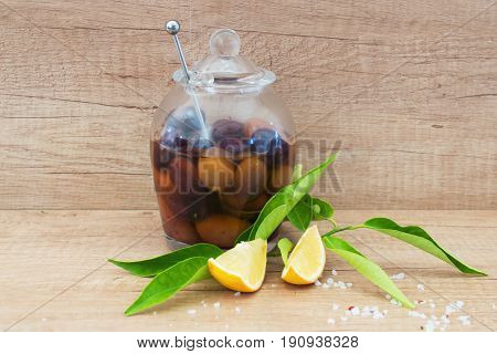A glass bowl with olives in olive oil on a wooden background with lemon, sea salt. Traditional greek food. Mediterranian lifestyle