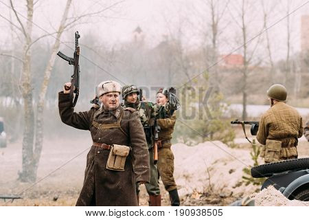 Gomel, Belarus - November 26, 2016: Re-enactor Dressed As Russian Soviet Red Army Soldiers Of World War II Celebrating Victory And Salute From Weapon In Air During Historical Reenactment.