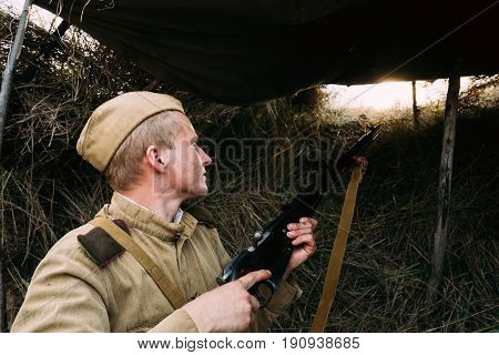 Dyatlovichi, Belarus - October 1, 2016: Reenactor Dressed As Russian Soviet Red Army Soldier Of World War II Hidden Sitting And Aiming Rifle Weapon From Trench, Hovel, Ambush In Autumn Meadow