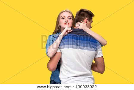 Portrait of a young couple standing against yellow studio background and Calling for silence