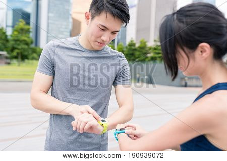 Woman and man using smart watch and get running together