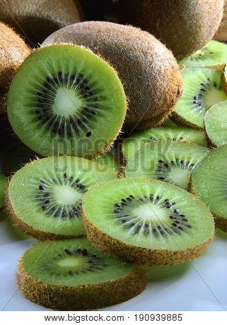 Coseup of brown kiwi fruit with green kiwi slices.