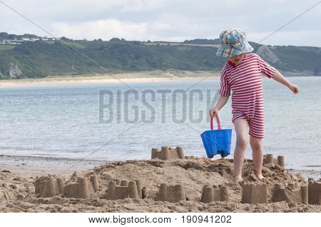 Oxwich beach, Wales, 14-08-2010: A young kid building a sand castle on the beach in Wales.