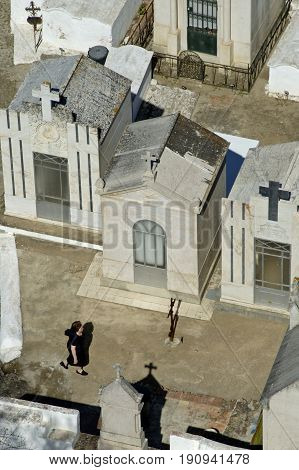 Alentejo, Portugal, 25-September-2007: A woman walking past the graves of a cemetery in Mertola village.