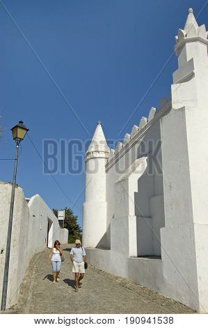 Alentejo, Portugal, 25-September-2007: A middle aged couple walking past an incredible white building in Mertola village.