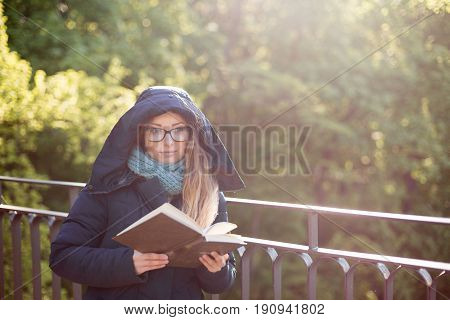 Happy Girl Reading A Book At The Railing.
