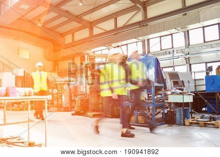 Blurred motion of business people wearing reflective clothing walking in metal industry