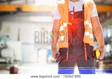 Midsection of young manual worker holding ear protectors and gloves in metal industry