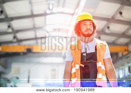 Young manual worker wearing protective clothing looking away in metal industry