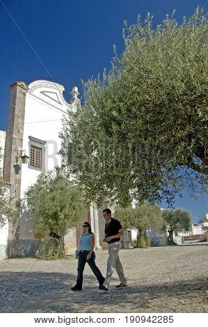 Alentejo, Portugal, 25-September-2007: A couple walking past buildings and beneath trees in Mertola village.