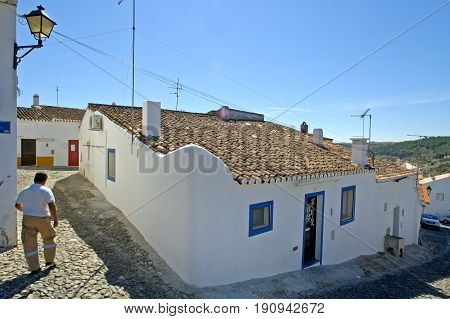 Alentejo, Portugal, 25-September-2007: A man walking past a lovely traditional house in Mertola village.