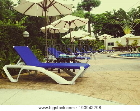 Sunbeds and umbrella in swimming pool garden - vintage filter effect.