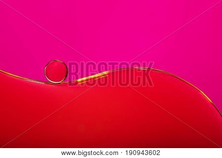 Oil drops in water bubble on pink abstract background