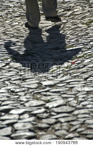 Alentejo, Portugal, 25-September-2007: A man's shadow follows him as he walks along the rocky streets of Mertola village.