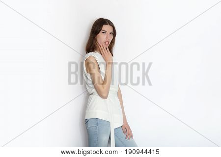 Young beautiful brunette beginner model woman practicing posing showing emotions on white wall studio background