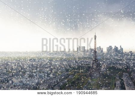 Paris skyline with Eiffel Tower at sunset on a cloudy day. La Defense business district can be seen in the distance behind the tower. Shot taken  through window with raindrops.