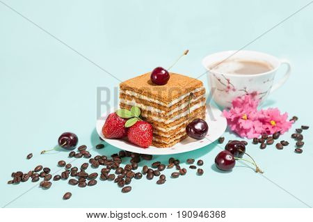 Tasty cake on the white plate and cup of coffee with cream, decorated with flowers, coffee beans, strawberries and ripe cherry on the light mint background with place for text, perspective view