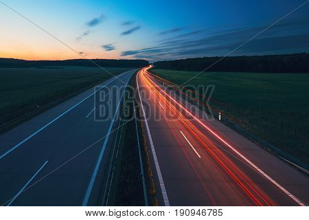 Tail lights of the cars during sunrise on the highway. Transportation and cars theme.