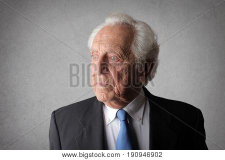 Elegantly dressed elderly man looking away