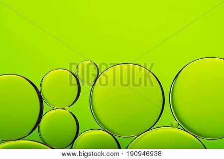 Oil drops in water bubbles on green abstract background