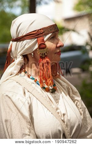 Khabarovsk Russia - June 11 2017: Middle ages period costume - senior Caucasian woman dressed in simple white dress. Poor lady peasant white canvas dress and ornaments. Historic medieval reenactment