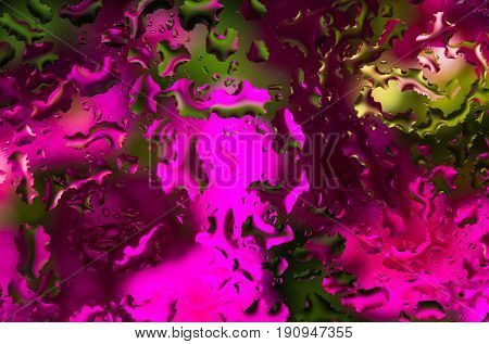 Water drops on glass with pink green background abstract rainy wall