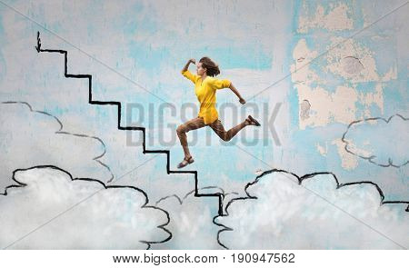 Young woman stepping on a imaginary staircase above the clouds