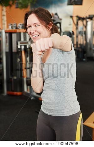 Very motivated woman at the gym with clenched fist having fun