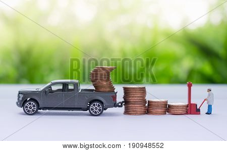 Miniature truck carrying stack of coins worker loading stack of coins using as a business concept.