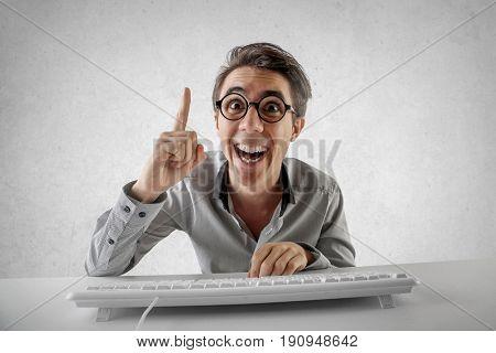 Employee sitting at his desk having a brilliant idea