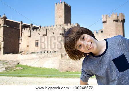 Beautiful 11 years old boy posing and smiling over ancient spanish castle Javier, Navarre, Spain. Cultural and historical spanish heritage. Young tourist making selfie agains architectural sight.