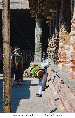 Hampi, India - November 20,2012: Unidentified Indian man with a drum stands in the courtyard of the Virupaksha temple. Several times of a day bells are sounding they echo buglers and drummers.