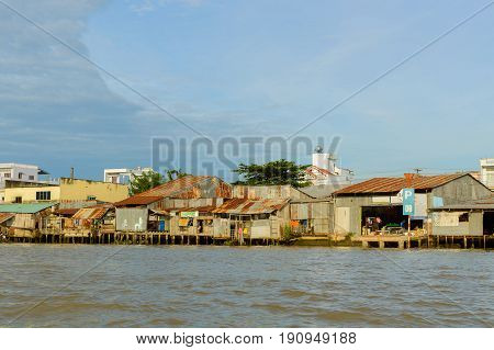 Delta of Mekong river poor residential houses shacks hovels on the bank of river