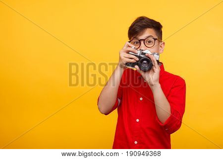 Boy in glasses and red shirt holding photo camera on yellow background.