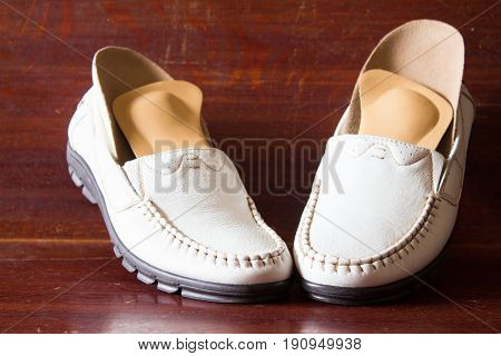 White Leather Slipper Or Shoes With Orthopedic Insoles. Wooden Background.