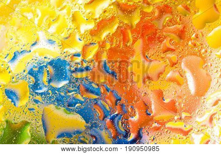 Water drops on glass with green blue orange background colorful abstract rainy